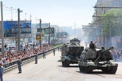 La gente mira en el armamento y el tanque en el camino fotografía de archivo