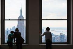 La gente mira hacia fuera sobre el horizonte de Manhattan, New York City Imagen de archivo libre de regalías