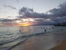 La gente mira puesta del sol dramática en la playa de San Souci Foto de archivo