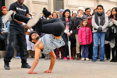 La gente mira un streetdancer sin hogar el hacer de breakdance y baila movimientos en las calles de París Imagenes de archivo