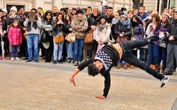 La gente mira un streetdancer sin hogar el hacer de breakdance y baila movimientos en las calles de París de ganar un poco de din Foto de archivo libre de regalías
