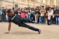 La gente mira un streetdancer sin hogar el hacer de breakdance y baila movimientos en las calles de París de ganar un poco de din Fotos de archivo