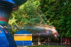 La gente monta en un oscilación en un parque de atracciones Imágenes de archivo libres de regalías