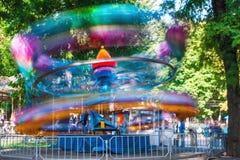 La gente monta en un oscilación en un parque de atracciones Fotografía de archivo libre de regalías