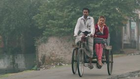 La gente monta las bicicletas por la calle en una mañana de niebla fría en Puthia, Bangladesh almacen de metraje de vídeo