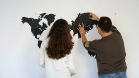 La gente monta un mapa del mundo en una pared blanca almacen de video