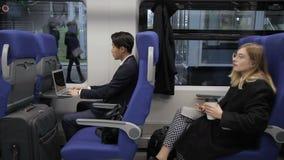 La gente multiethnical se está sentando en el tren que se está colocando en la estación almacen de video