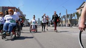La gente negli atleti delle sedie a rotelle che partecipano alla maratona Movimento lento archivi video