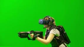 La gente nei caschi di VR gioca il gioco nella realtà virtuale su un fondo verde archivi video