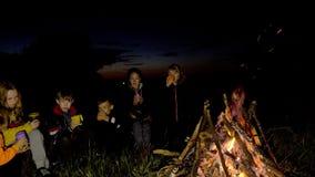 La gente nel campo sta riscaldando dal fuoco stock footage