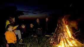 La gente nel campo sta riscaldando dal fuoco archivi video