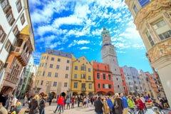 La gente nel centro urbano di Innsbruck sotto Stadtturm si eleva Immagini Stock Libere da Diritti