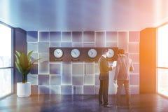 La gente nell'ingresso grigio dell'ufficio con gli orologi fotografia stock libera da diritti