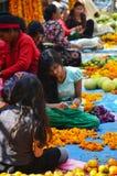 La gente nepalesa hace la guirnalda para la venta en el mercado de Thamel fotos de archivo