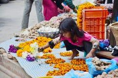 La gente nepalesa hace la guirnalda para la venta en el mercado de Thamel fotografía de archivo libre de regalías