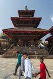 La gente nepalese passa un tempio indù che ha danneggiato dal terremoto, Kathmandu, Nepal immagini stock libere da diritti