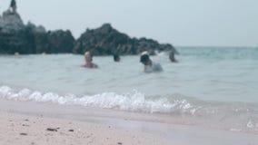 La gente nuota nell'ondeggiamento dell'oceano infinito contro la roccia marrone video d archivio