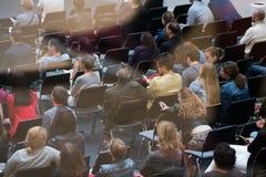 La gente partecipa alla conferenza di vendita di Digital in grande corridoio Fotografia Stock
