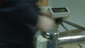 La gente pasa el torniquete electrónico con la tarjeta plástica en la oficina almacen de video