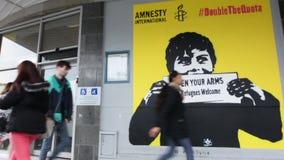 La gente pasa por la pintada con los refugiados políticos Welcom del lema