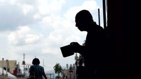 La gente pasa por las limosnas que buscan de un viejo mendigo masculino ciego en el portal de la iglesia almacen de video