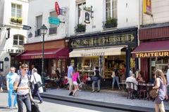 La gente pasa por un café en la calle de Rue Montorgueil Imagenes de archivo