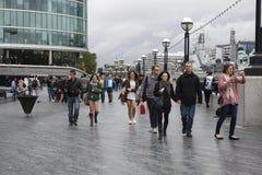 La gente pasa a través del cuadrado de Leicester después de lluvia Fotos de archivo