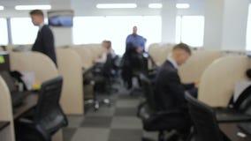 La gente passa attraverso il grande ufficio dello spazio aperto diviso con le lunghe file di scrittori funzionanti archivi video