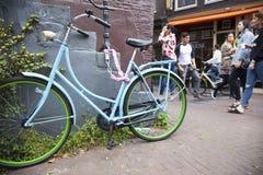 La gente passa la vecchia bicicletta blu e verde a Amsterdam del centro tutta Immagine Stock Libera da Diritti
