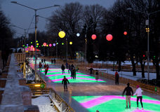 La gente passare la sera alla pista di pattinaggio colorata Fotografie Stock