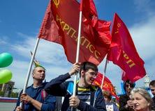 La gente porta le bandiere rosse sulla dimostrazione di festa dei lavoratori Fotografie Stock Libere da Diritti