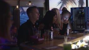 La gente que anima en la barra se coloca en partido en club nocturno danza holidays bebidas almacen de metraje de vídeo