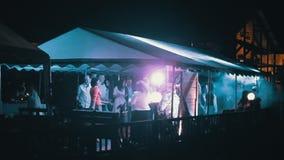 La gente que baila en la playa va de fiesta debajo de la tienda en la noche