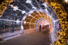 La gente que camina con los días de fiesta del Año Nuevo y de la Navidad enciende el túnel en el centro de ciudad en Moscú Foto de archivo libre de regalías