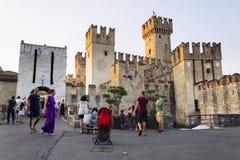 La gente que camina delante de Scaliger se escuda el 30 de julio de 2016 en Sirmione, Italia Imagenes de archivo