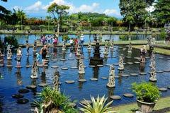 La gente que camina en las piedras en Tirtagangga riega el palacio Foto de archivo