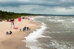 La gente que camina en la playa entre ondas enormes justo antes de una tormenta grande, el cielo es llena de nubes oscuras imagenes de archivo