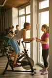 La gente que ejercita en las bicis inmóviles en aptitud clasifica fotografía de archivo libre de regalías