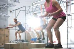 La gente que hace la caja salta ejercicio en gimnasio del crossfit Foto de archivo