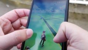 La gente que juega Pokemon VA el teléfono elegante aumentado golpe app de la realidad almacen de metraje de vídeo