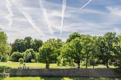 La gente que merienda en el campo en un parque entre árboles, avión se arrastra en el cielo imagen de archivo