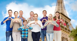 La gente que muestra la mano del corazón firma encima la torre Eiffel Imágenes de archivo libres de regalías
