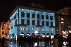 La gente que recorría cerca de la construcción maravillosamente adornó con las luces Imagen de archivo libre de regalías