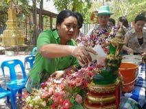 La gente que riega la estatua de Buda el día de Songkran, Foto de archivo libre de regalías