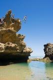 La gente que salta de un acantilado en piscina de la roca Fotos de archivo libres de regalías