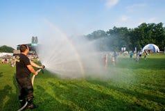 La gente que salta debajo de la agua corriente del bombero en el partido al aire libre Imágenes de archivo libres de regalías