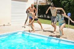 La gente que salta a la piscina Imagenes de archivo