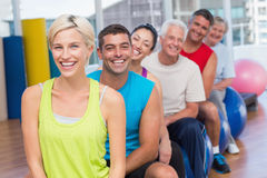 La gente que se relaja en bolas del ejercicio en gimnasio clasifica Imagen de archivo
