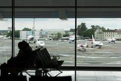 La gente que se sienta en el aeropuerto gandulea para el embarque que espera en una f Foto de archivo