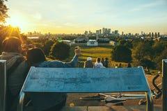 La gente que se sienta en el top de la colina en Greenwich parquea, Londres, mirando la puesta del sol y tomando las fotos imagen de archivo